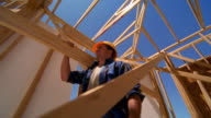 Low angle medium shot tracking shot construction worker carrying wooden beam while walking through frame of house / Texas