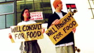Low angle medium shot two men stand outdoors with signs reading 'will program/consult for food' / San Francisco