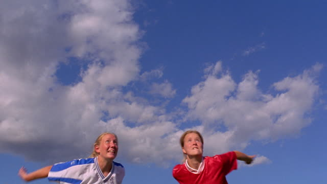 Low angle medium shot two teenage girls jumping and competing for header during soccer match / Vermont