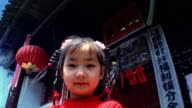 Low angle medium shot young Asian girl with pig tails standing in front of building with Chinese signs / China