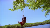 Low angle medium shot young boy swinging and jumping into lake from rope