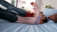 Low angle medium shot young woman jumping into boyfriend's arms / couple falling onto bed / South Africa