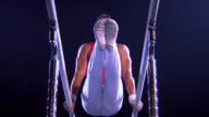 Low angle medium shot zoom in zoom out male gymnast mounting parallel bars, peforming routine and dismounting