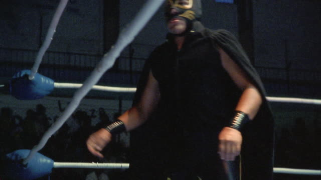Low angle medium shot zoom out luchador 'Lince' warming up for match in corner of ring / Queretaro, Mexico