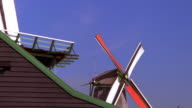Low angle medium shot zoom out windmills / Holland