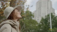 Low angle medium tracking shot of young woman looking up at trees and highrises / New York City, New York, United States