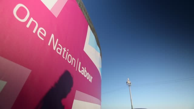 Low Angle Mid Shot people passing by Labour branding