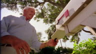 low angle MS middle-aged man getting mail out of mail box + shaking head unhappily