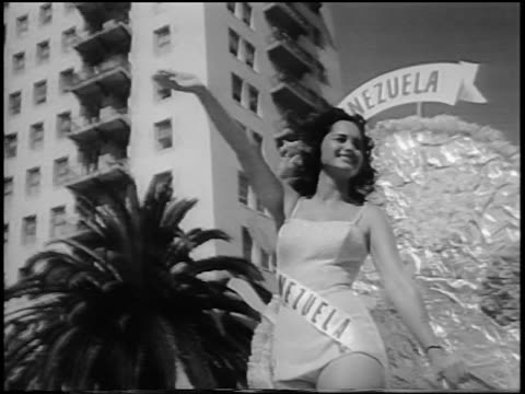 B/W 1956 low angle PAN Miss Venezuela waving from float in Miss Universe beauty parade / Long Beach CA