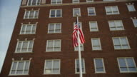 Low angle, multistory, brick building with American flag flying