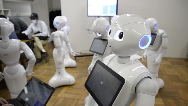 Low angle MWS attendees work with humanoid robots named Pepper developed by SoftBank Corp's Aldebaran Robotics unit during a Softbank developer's...