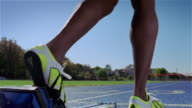 Low angle of track and field athlete placing feet on starting block during training session on outdoor track / taking off