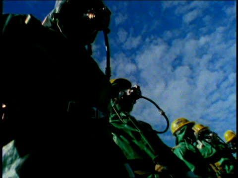 Low angle pan people wearing protective suits and gas masks / Hanford, Washington