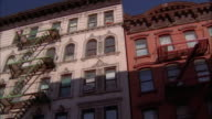 Low angle pan tops of tenement apartment buildings / NYC