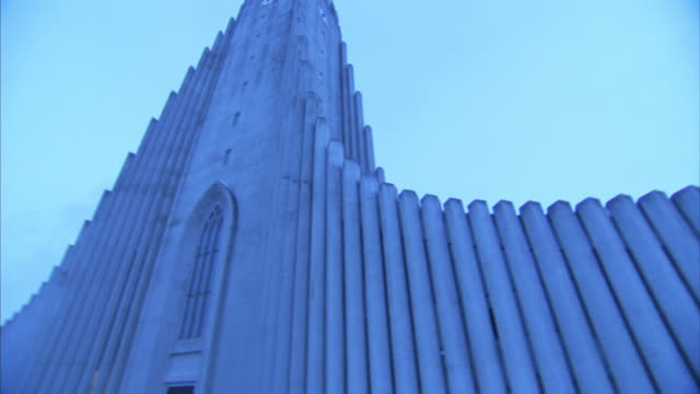 Low Angle pan-left - A modern cathedral contrasts against a pale blue sky. / Reykjavík, Iceland