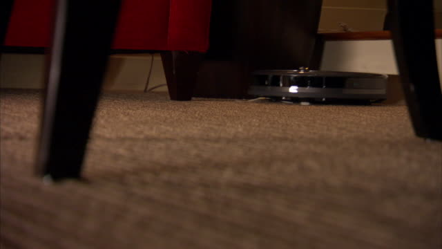 Low Angle pan-left tilt-down - A robot cleans a carpeted living room.