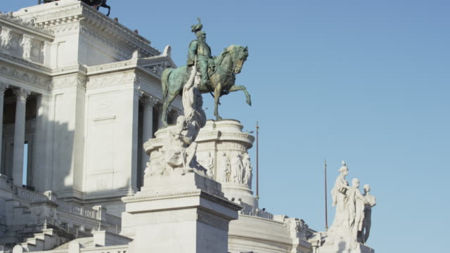 Low angle panning shot of statues on roof / Rome, Italy
