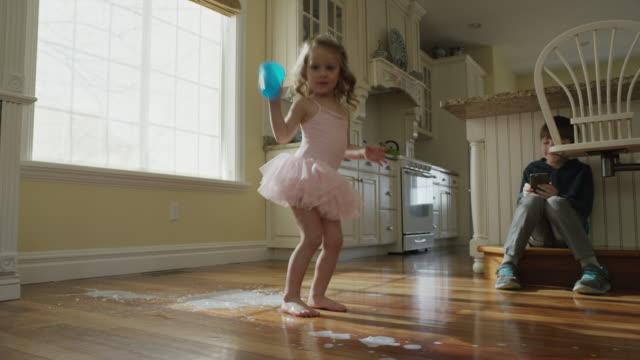 'Low angle panning slow motion shot of girl spilling milk on kitchen floor / Cedar Hills, Utah, United States'