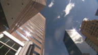 Low Angle pan-right - A Denver skyscraper reflects a sunburst below feathery clouds. / Denver, Colorado, USA