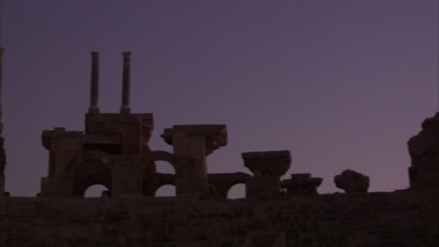Low Angle pan-right - Stone columns tower over a decorative wall. / Tripoli, Libya