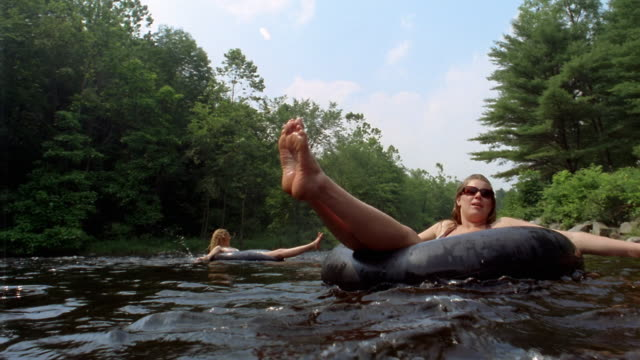 Low angle people riding innertubes on river