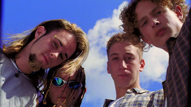 low angle PAN PORTRAIT four teen boys looking down at camera outdoors