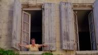 low angle PAN PORTRAIT woman pushing open window shutters quickly + smiling / St. Emilion, Bordeaux, France