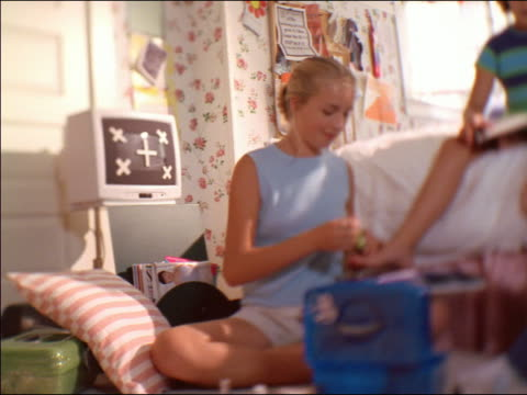 low angle SELECTIVE FOCUS three teen girls in bedroom looking at magazines, talking + painting toenails