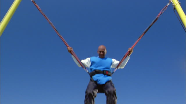 Low angle senior man jumping on bungee cords against blue sky