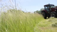 Low angle shot, a red tractor harvests hay from a field