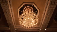 Low angle shot of a beautiful chandelier suspended from the ceiling in the hotels dinning room Available in HD