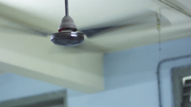 Low angle shot of a ceiling fan in motion.