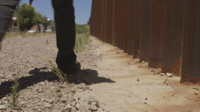 Low angle shot of a man walking along a section of the border fence between Mexico and the United States.
