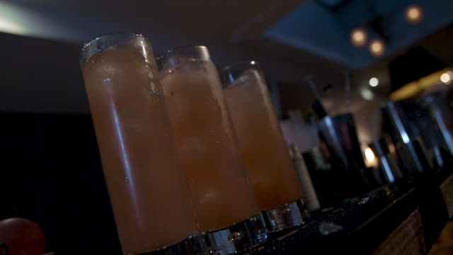 Low angle shot of cocktails being made in a bar.