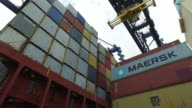 Low angle shot of cranes lifting containers off the deck of a container ship at the port of Felixstowe