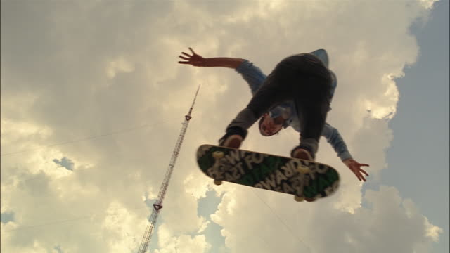 Low angle shot of pole against clouds in sky / slow motion of skater performing ollie over camera