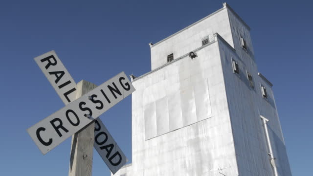 Low Angle Shot of Railroad crossing sign & grain building