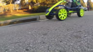 Low angle shot on go-cart wheels drive by with boy driving on  residential road.