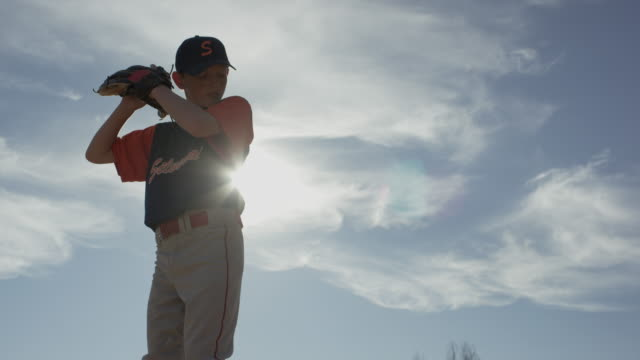 Low angle slow motion medium shot of pitcher throwing baseball / American Fork, Utah, United States