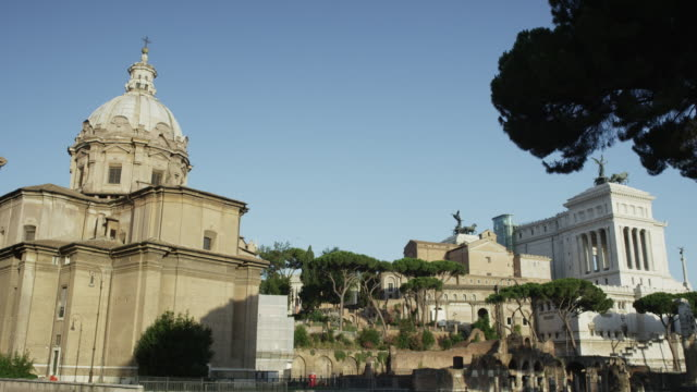 Low angle slow motion wide panning shot of buildings and statues in ancient ruins / Rome, Italy