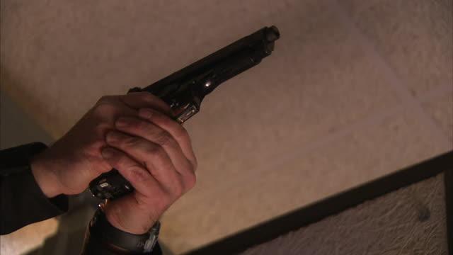 Low Angle static - A man's hands raise a gun, then fires it.