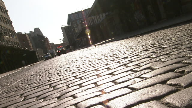 Low Angle static - A tow truck pulls a vehicle over a cobblestone street. / New York City, New York, USA