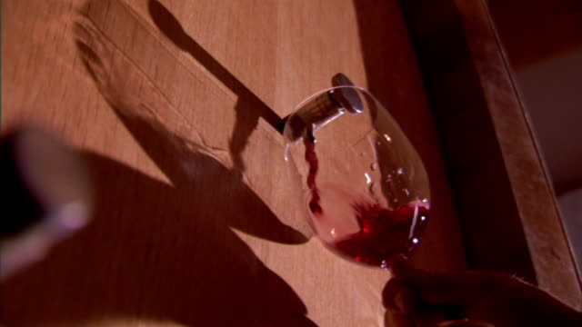 Low Angle static - A wine tap fills a glass with red wine. / Sicily, Italy