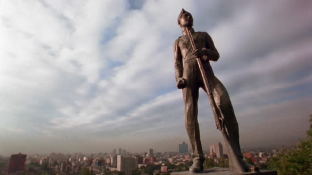Low angle statue of soldier w/Mexico City skyline in background