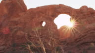 Low angle, sun recedes behind large arch structure in Utah