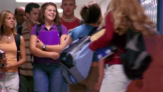 Low angle teenage students walking in school hallway
