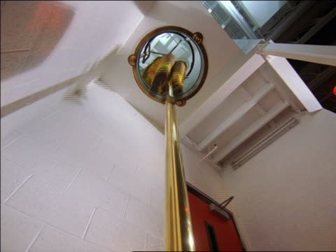 low angle three firefighters sliding down pole in fire station