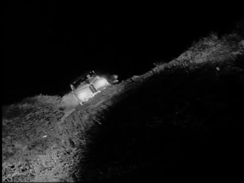 B/W 1947 low angle tilt down PAN Packard driving off road then flipping down hill at night