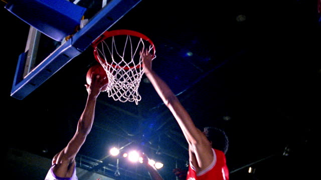 low angle tilt up two men's basketball teams under basket as Black man does lay-up, scores + snarls at camera