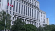 Low Angle tilt-up - A Canadian flag flies in front of a large government building. / Canada